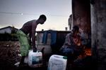 Michele Palazzi & Alessandro Penso: Migrant Workers Warming up Water to Wash Themselves, Basilicata, Italy